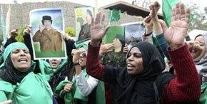 Simpatizantes de Muamar al Gadafi sostienen carteles con su fotografía durante una manifestación.