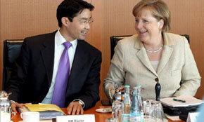 El nuevo ministro de Economía alemán, Philipp Rösler (izq), conversa con la canciller alemana, Angela Merkel