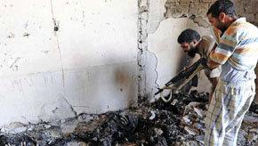 Rebeldes contemplan los cadáveres carbonizados de insurgentes a las afueras de Trípoli.