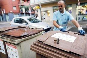 Un obrero maneja contenedores de basura con candados, en un supermercado