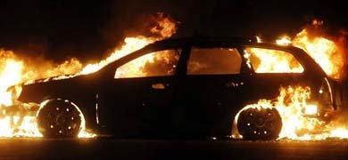 Un automóvil arde al lado de una de las barricadas levantadas por los manifestantes.