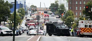 Agentes de la Policía y un helicóptero buscan a uno de los tiradores en la base de la Marina
