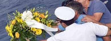 Un pescador y un oficial de un crucero lanzan un ramo de flores al mar como muestra de respeto tras el drama de Lampedusa, donde murieron más de 130 inmigrantes