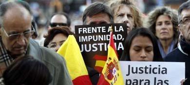 Varias personas sostienen carteles durante la concentración convocada por DENAES. (EFE)