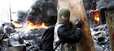 Un manifestante opositor se protege durante los disturbios en Kiev, la capital de Ucrania (Reuters).