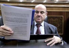 El ministro de Economía, Luis de Guindos, se dispone a guardar unos papeles en su cartera.