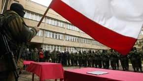 Un hombre armado, supuestamente un soldado ruso, ondea una bandera de Rusia en Simferópol, capital de Crimea (Reuters).