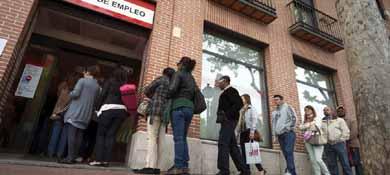 Un grupo de personas hace cola en una oficina del INEM en Alcalá de Henares. (EFE)