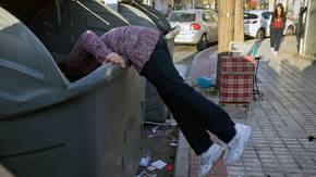 Una persona busca comida en un contenedor/ LUIS SERRANO