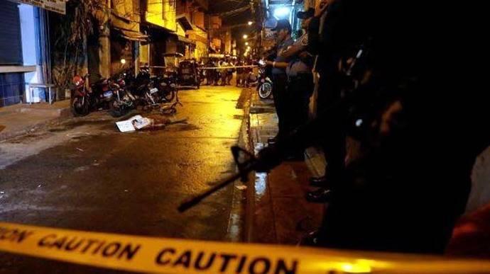 Policías rodean el cuerpo de una persona muerta durante un operativo antidrogas en el Metro de Manila