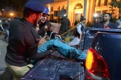 Uniformados trasladan a uno de los heridos en Lahore.