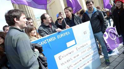 Pablo Iglesias en Berlín con una tarjeta sanitaria gigante