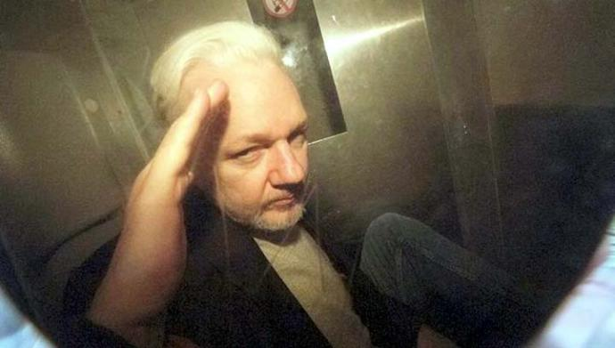Julian Assange hace un gesto de saludo a los periodistas al salir del tribunal