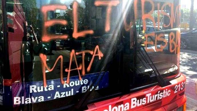 Imagen del bus turístic con la pintada 'El turismo mata los barrios'