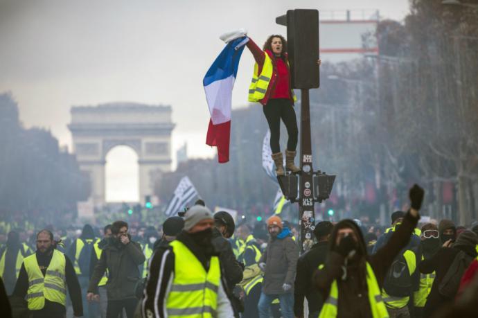 """Una mujer, parte de los """"chalecos amarillos"""" grita consignas subida a un semáforo durante una protesta en los Campos Elíseos en París, Francia."""