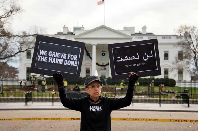 Una mujer protesta por la decisión de Trump, a las afueras de la Casa Blanca.
