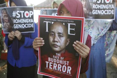 Varios manifestantes sostienen pancartas a con la imagen del monje budista Wirathu