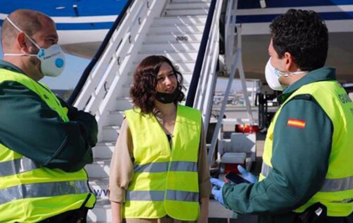 Isabel Díaz Ayuso al pie de un avion en el aeropuerto de Madrid