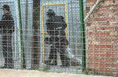 Un agente de la Policía Nacional arrastra a un inmigrante herido al otro lado de la valla de Melilla./ Blasco de Avellaneda