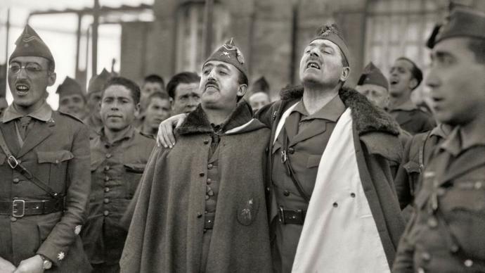 """Francisco Franco y Millán Astray, abrazados mientras entonan cánticos legionarios. Cuartel de Dar Riffien"""". Fotografía de 1926."""