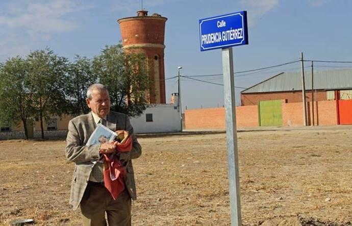 José Antonio Sierra Lumbreras junto al indicador del nombre de la calle Prudencia Gutiérrez en Crespos, Ávila, que promovió en reconocimiento al altruismo de esta vecina del municipio