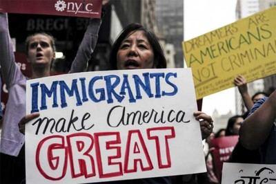 Una manifestante con un cartel que dice 'los inmigrantes hacen grande a América', refiriéndose al slogan de campaña de Trump: Make America Great Again.