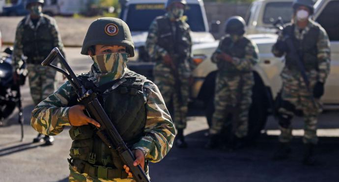 Los militares de la Guardia Nacional Bolivariana vigilan una autopista a la entrada de Caracas