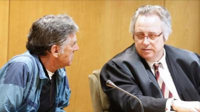 Enrique Olivares charla con su abogado durante el juicio