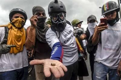 Activistas de la oposición muestran un casquillo de bala durante una manifestación contra el gobierno del presidente Nicolás Maduro a lo largo de la carretera de Francisco Fajardo en Caracas.