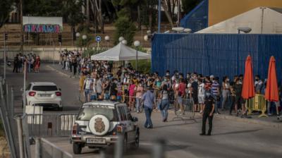 Decenas de personas esperan su turno en la entrada de la comisaría de extranjería de Aluche.Olmo Calvo