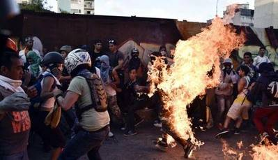 Un hombre corre envuelto en llamas luego de ser golpeado por manifestantes de la oposición de Venezuela en Caracas.