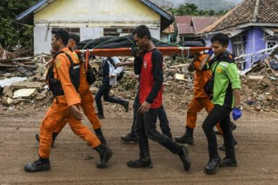 Miembros de un equipo de rescate de Indonesia cargan un cadáver durante la búsqueda de víctima que dejó el Tsunami del 22 de diciembre.