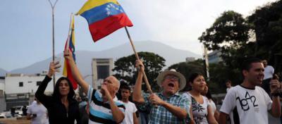 Simpatizantes del presidente interino Juan Guaidó ondean banderas este martes en la base militar La Carlota