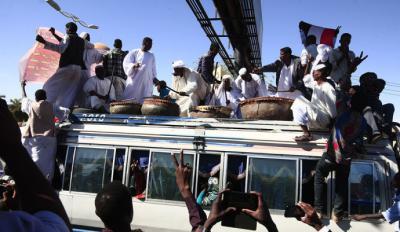 Manifestantes sudaneses en el techo de un autobús