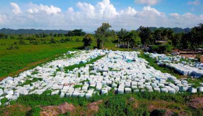 Miles de botellas de agua donadas, aparecen en una finca