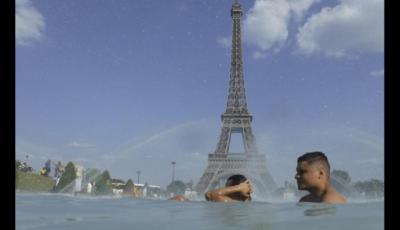 n grupo de personas se refresca en una fuente en París, Francia.
