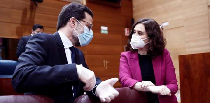 La presidenta de la Comunidad de Madrid, Isabel Díaz Ayuso (d) conversa con el consejero de Hacienda, Javier Fernández-Lasquetty (i) antes del comienzo de la sesión de control al ejecutivo regional en la Asamblea de Madrid.