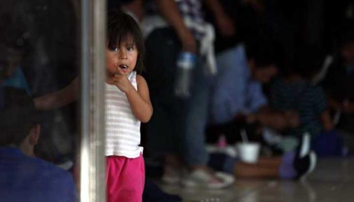 Una niña migrante, cuya familia espera llegar a Estados Unidos, mira a la cámara mientras sus padres esperan en un centro de inmigración en México.