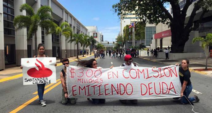 Un grupo de estudiantes sostiene una pancarta contra el Banco Santander en San Juan, Puerto Rico